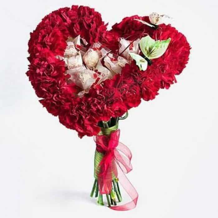 букет из красных гвоздик с конфетами в виде сердца